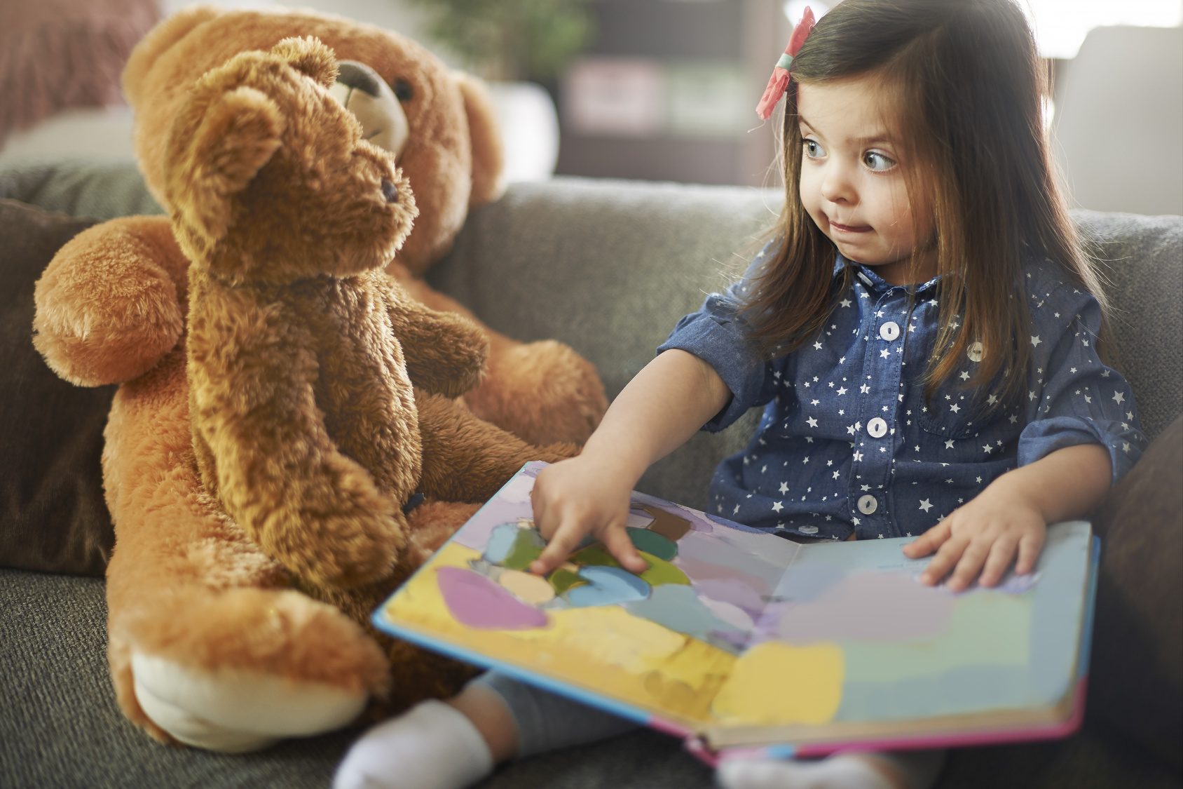 zdjęcie przedstawiające dziewczynkę z książką uczącą misia